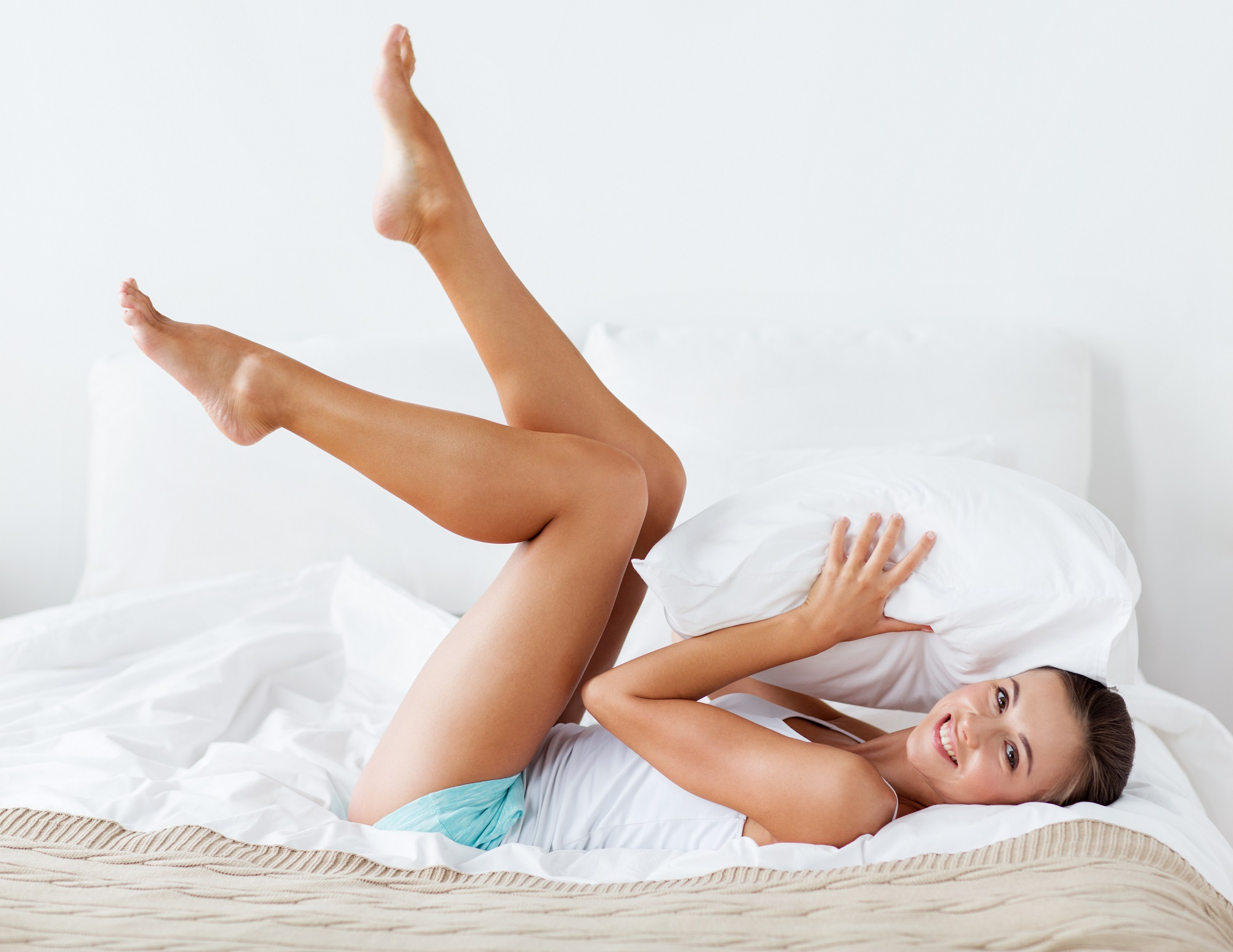 happy young woman with pillow lying in bed at home