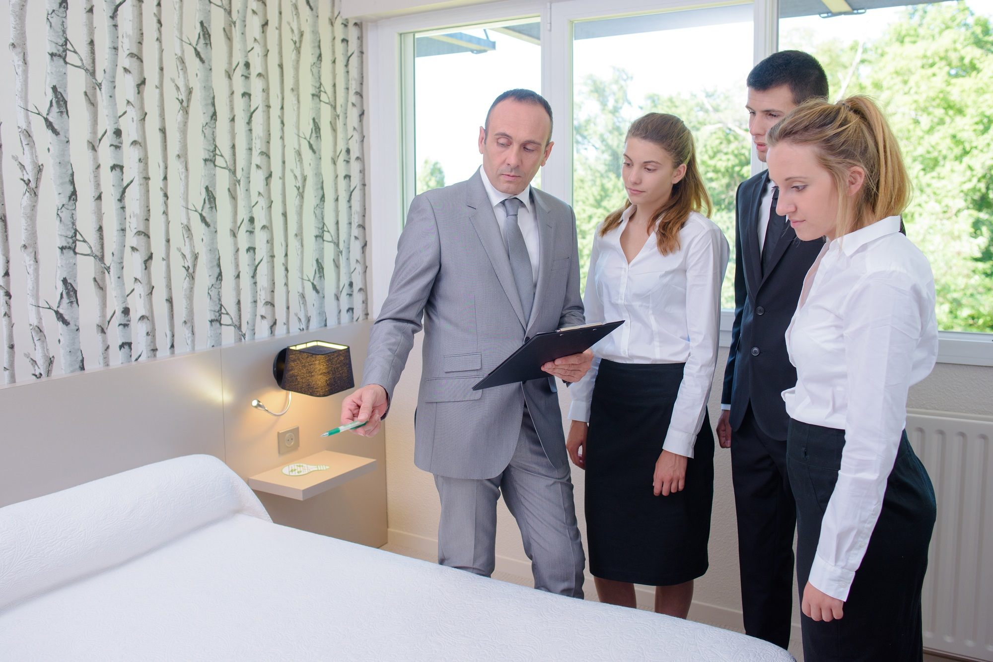 Supervisor in bedroom instructing hotel staff